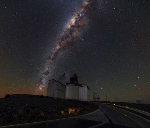 High up in the Chilean Atacama Desert, pioneering feats of human engineering collide with the majestic beauty of the natural world. This image shows ESO's La Silla Observatory, where domes housing some of the most advanced astronomical instruments in the world sit beneath a sky shimmering with stars. All of these stars belong to our home galaxy, the Milky Way. The Milky Way contains billions of stars, arranged in two strikingly different structures. The roughly spherical halo component, consisting mainly of older stars, appears in this image as the background of stars scattered across the sky. The second component is a thin disc made up of younger stars, gas and dust. We see this as a dense, bright, and visually stunning band running almost vertically across the sky. Pockets of dust block out the light from stars behind, giving the band a mottled appearance. The bright concentration in the band of stars, located toward the top centre of this image, is the central region of the Milky Way. Here, astronomers have measured stars moving very much faster than anywhere else in our galaxy. This is taken as evidence for a supermassive black hole, some four million times the mass of the Sun, at the very centre of our galaxy. The black hole cannot be observed directly, but its presence can be inferred from the effect its enormous gravity has on the motions of these nearby stars.